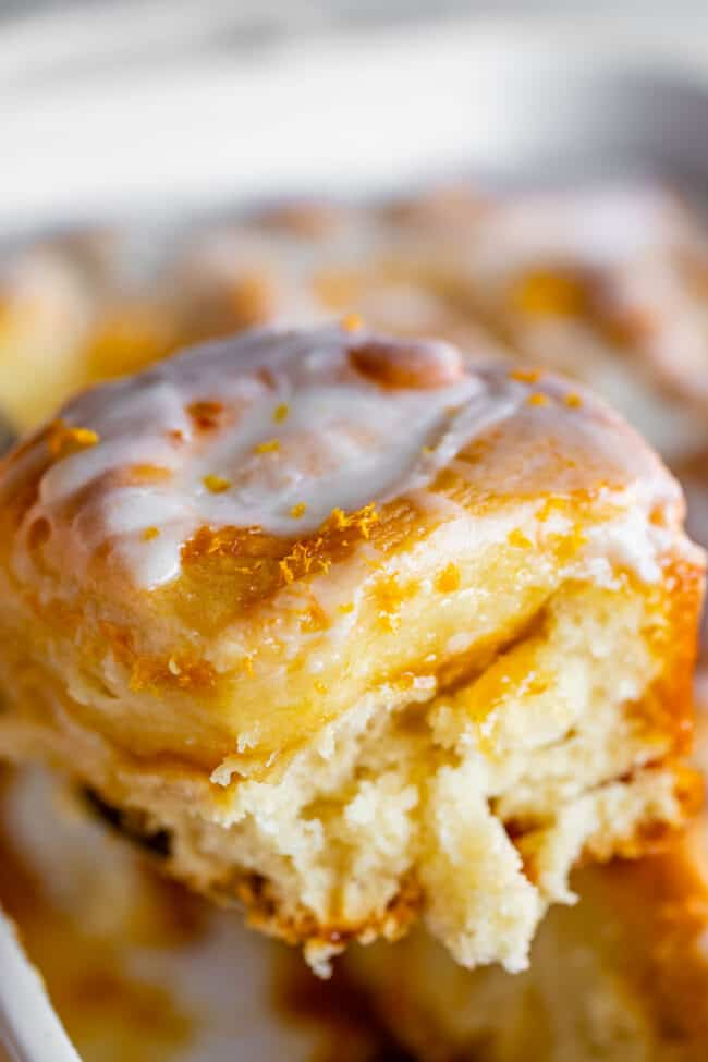 meyer lemon sweet roll with glaze being lifted on a spatula
