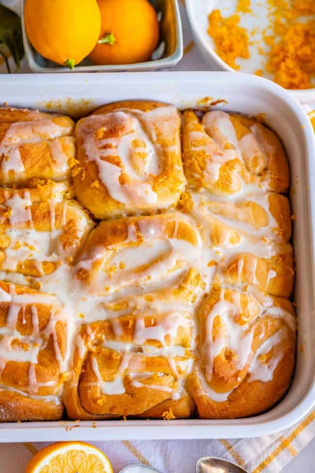 overhead photo of meyer lemon rolls in a 9x3 inch pan with lemons on the side