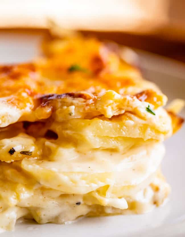 cheesy scalloped potatoes stacked on a plate
