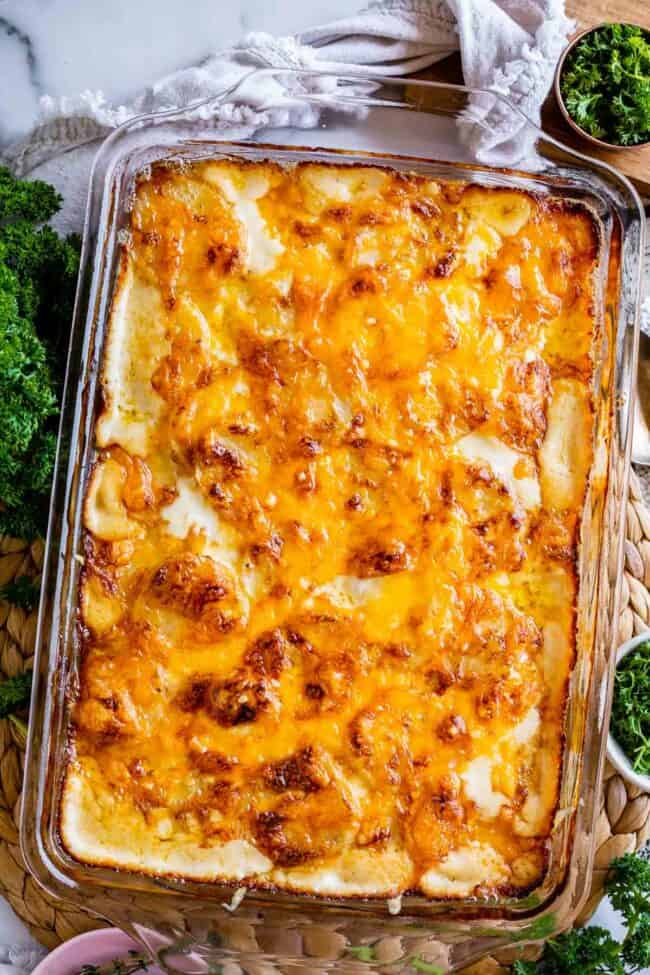 cheesy scalloped potatoes in a glass casserole dish with a tan napkin and parsley