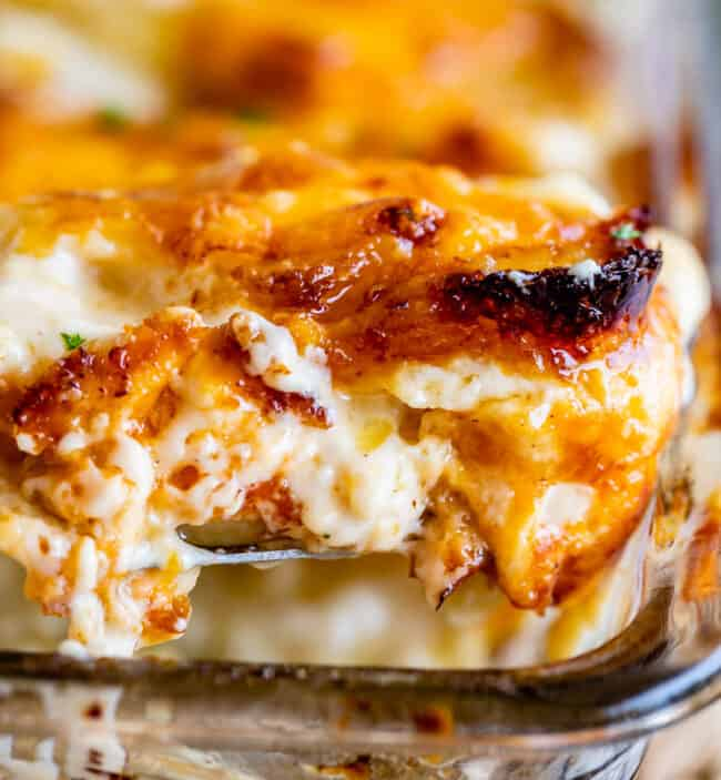 scalloped potatoes with crispy edges being lifted from a clear casserole dish