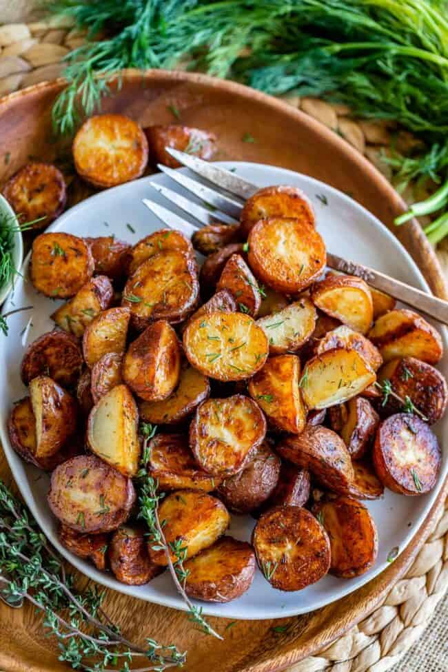 oven roasted red potatoes on a white plate placed on a wooden plate, with dill on the side