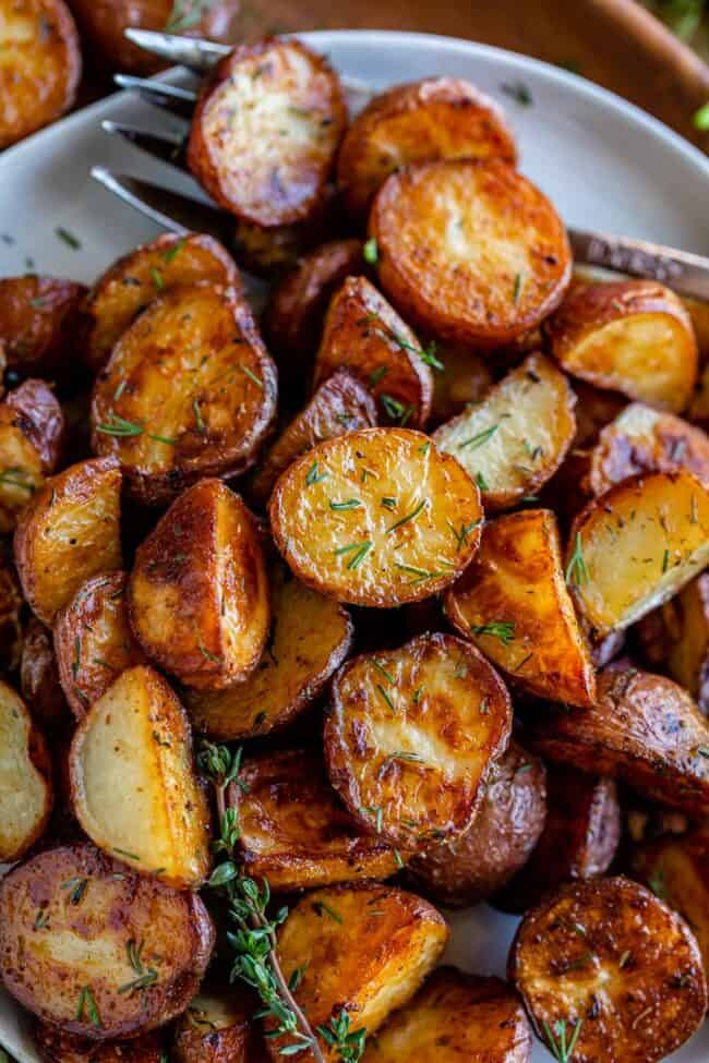 roasted red potatoes with dill on a white plate with a fork