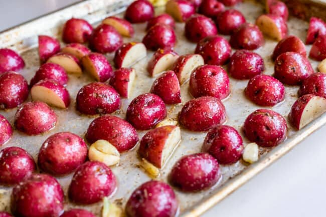 red skin potatoes arranged cut side down on a sheet pan