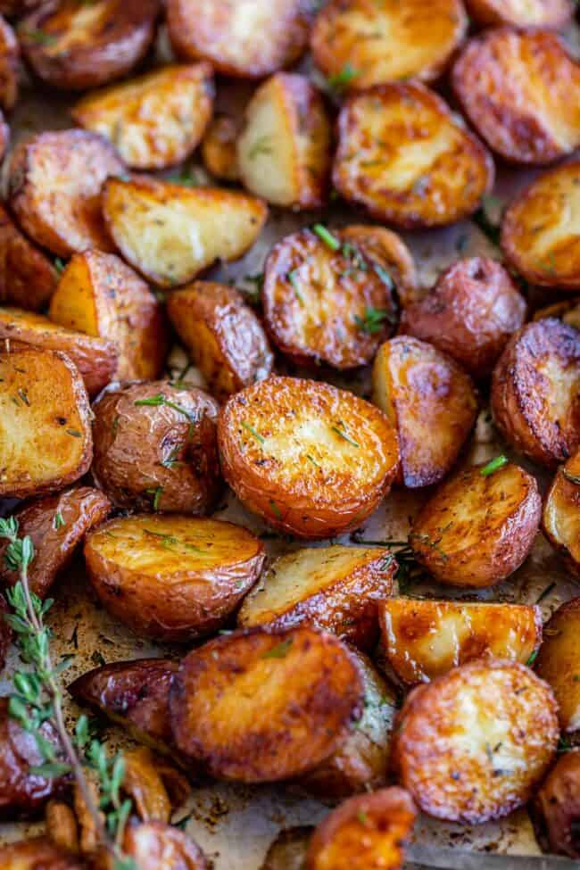 crispy roasted red potatoes on a sheet pan with herbs