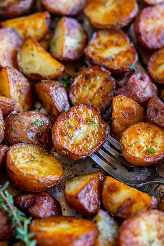 garlic roasted potatoes on a sheet pan with a fork and dill