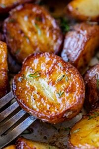 roasted red skin potatoes on a fork sprinkled with herbs