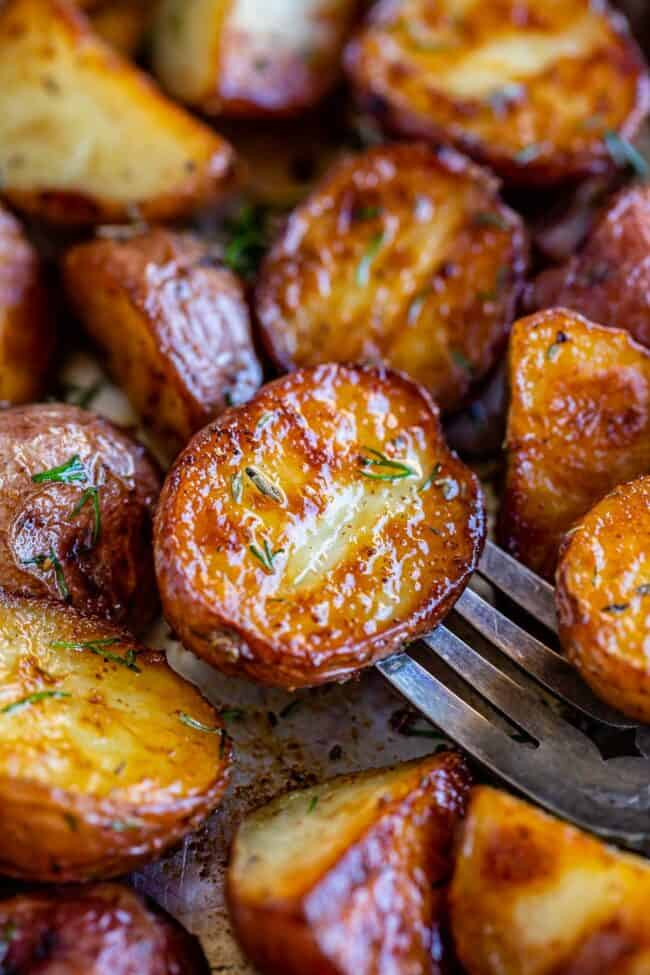 roasted red baby potatoes on a pan, one pierced with a fork