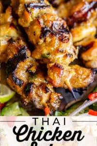 chicken satay skewers on a plate with cucumber slices