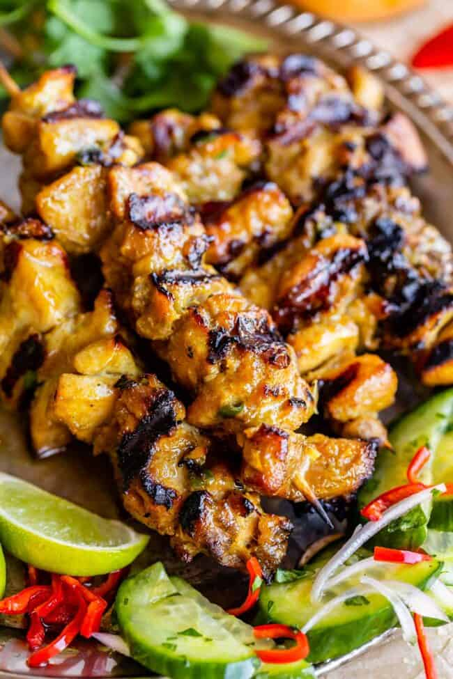 chicken satay recipe on a sliver plate with cucumber salad