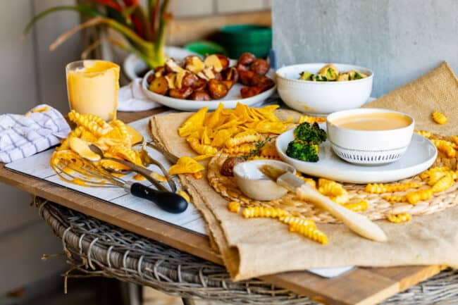photo shoot set up: fries, chips, broccoli, cheese dip on a wooden board with brown table runner