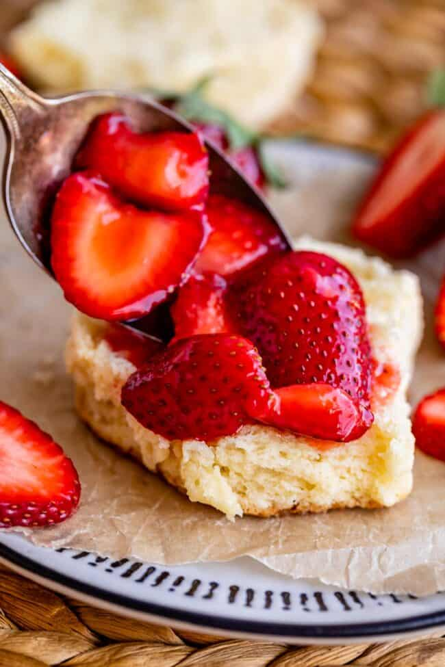 spooning strawberries onto shortcake on a plate