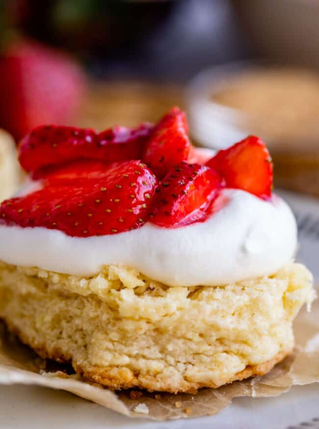 shortcake on parchment paper topped with whipped cream and strawberries