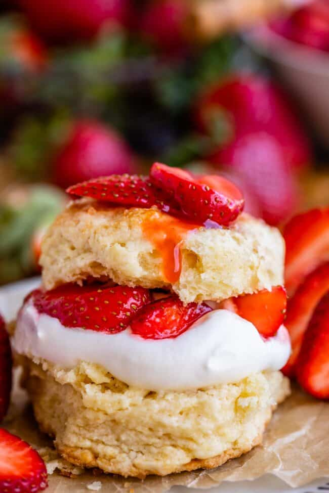 strawberry shortcake stacked on parchment paper on a plate with strawberries in the background
