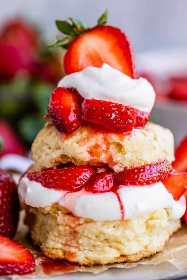 strawberry shortcake biscuits stacked together with strawberries and whipped cream