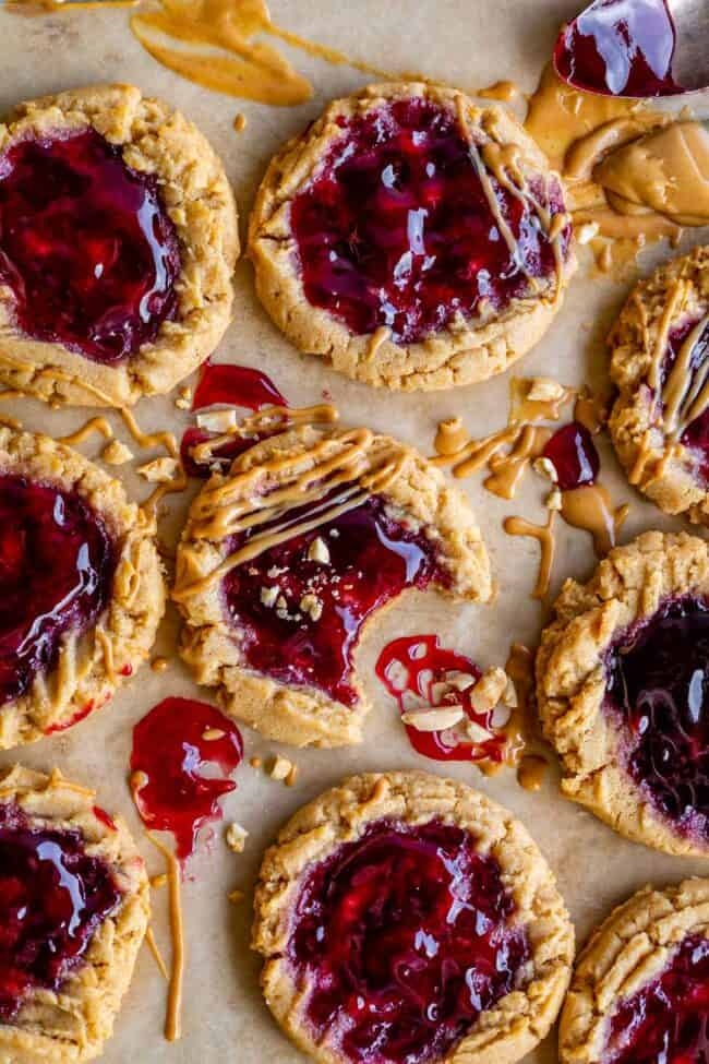 pb and j cookies on parchment paper with jam, peanut butter, chopped nuts garnish with