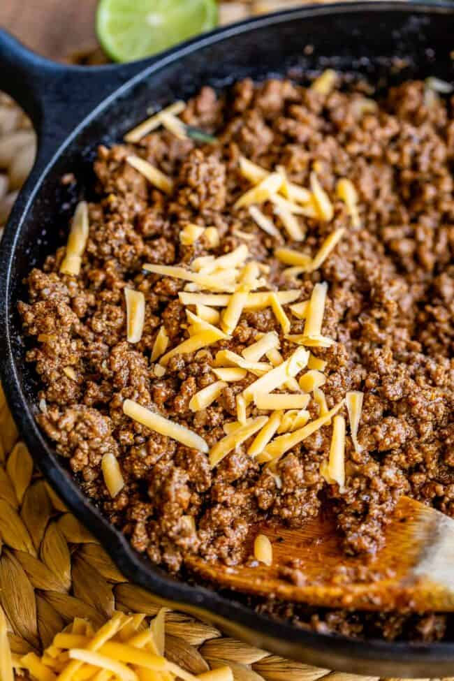 a cast iron pan full of taco meat, sprinkled with cheddar cheese