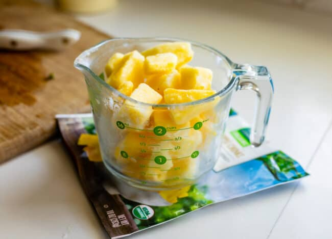 frozen pineapple chunks in a glass measuring cup
