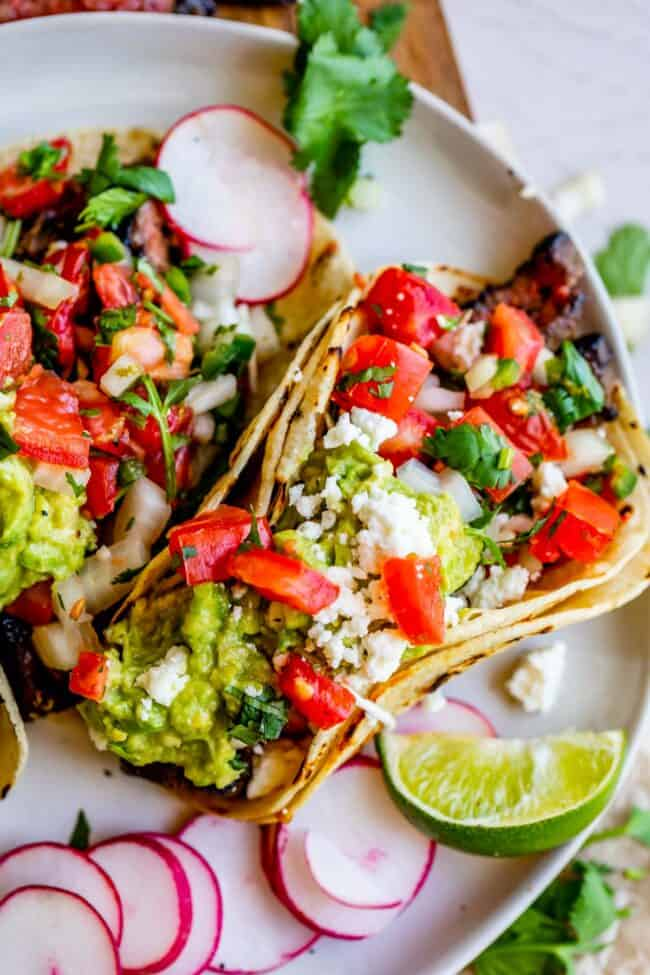 carne asada recipe in a taco, on a plate with radishes