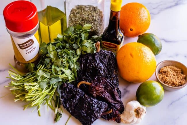 all the ingredients needed for a beef mojo marinade: cilantro, peppers, orange, lime, etc.