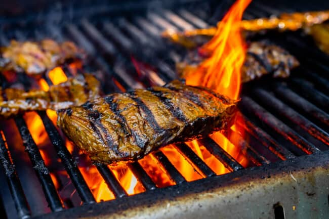 outside skirt steak on a grill with flames in the background