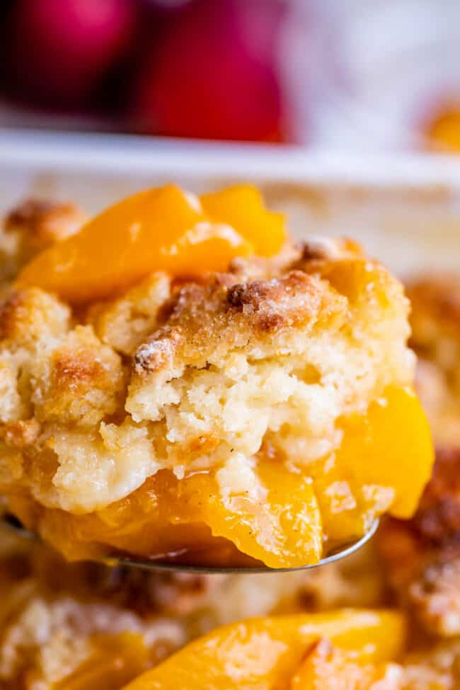 lifting peach cobbler out of the pan on a spoon