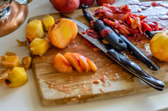 slicing peeled peaches on a cutting board