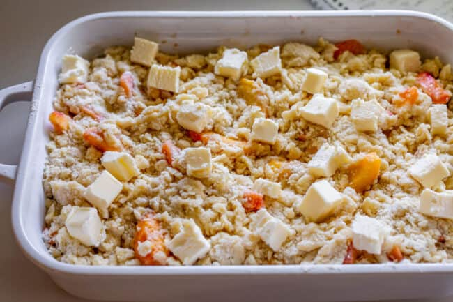 unbaked peach cobbler in a white casserole dish with cut butter on top