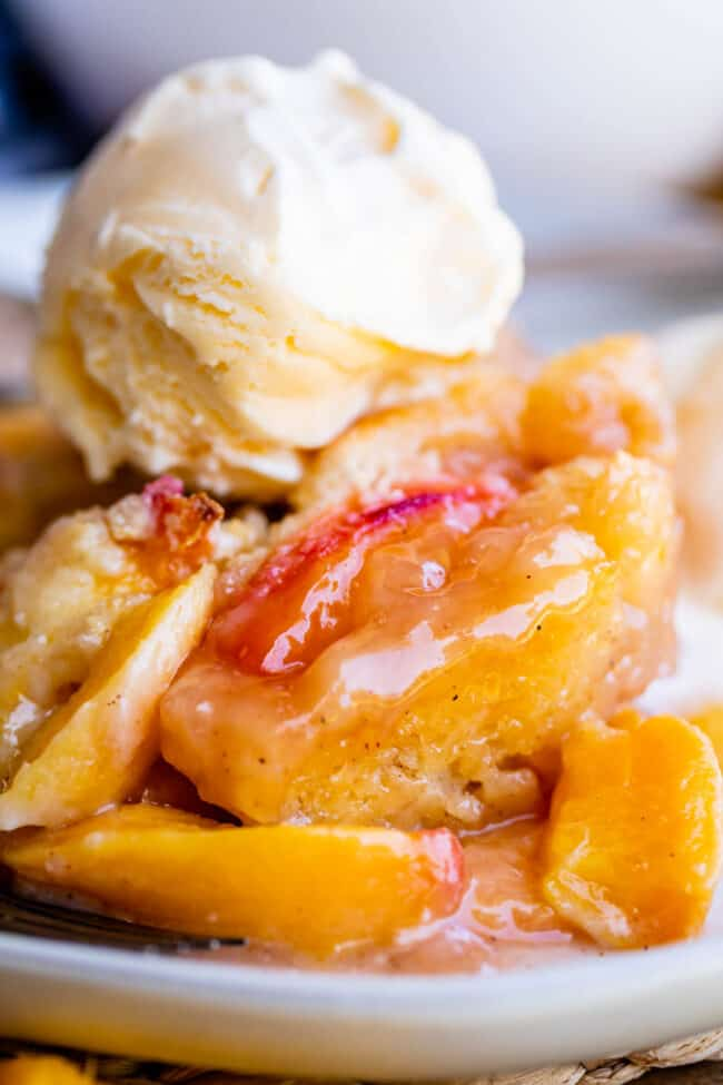 fresh peach cobbler on a plate topped with ice cream