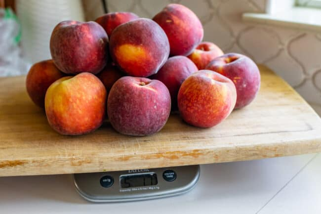 5 pounds of peaches on a cutting board on a scale