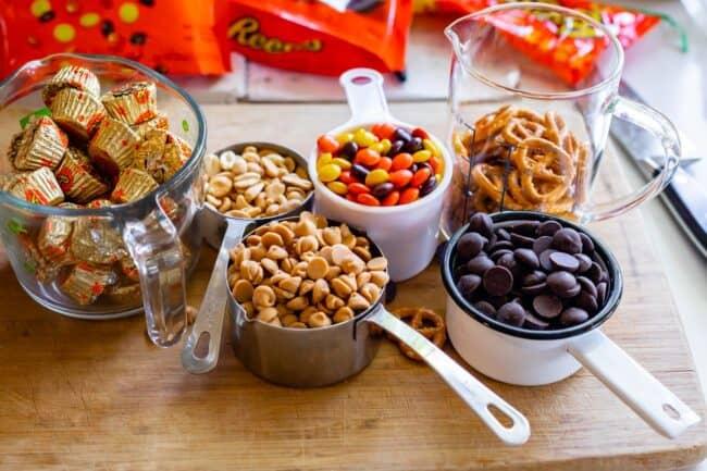 ingredients in measuring cups on a cutting board: Reese's cups, peanuts, pb chips, reeses pieces, chocolate chips