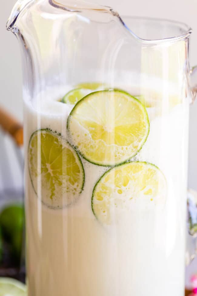 Brazilian lemonade in a pitcher with sliced limes