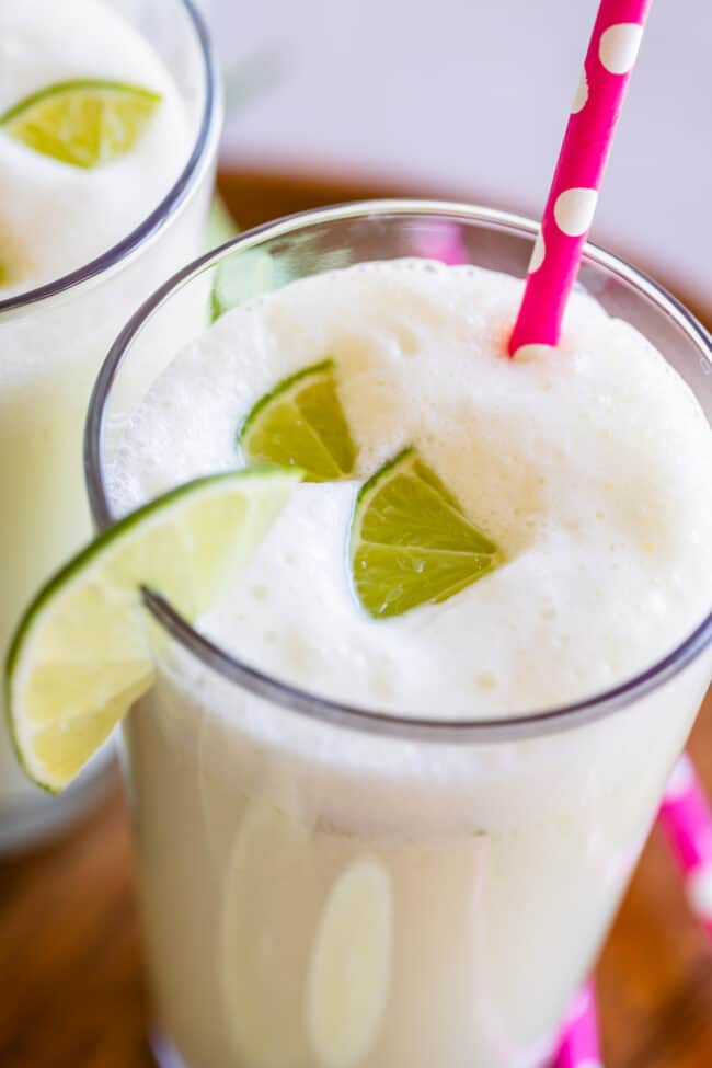 brazilian limeade in a glass with lime wedges and a pink straw