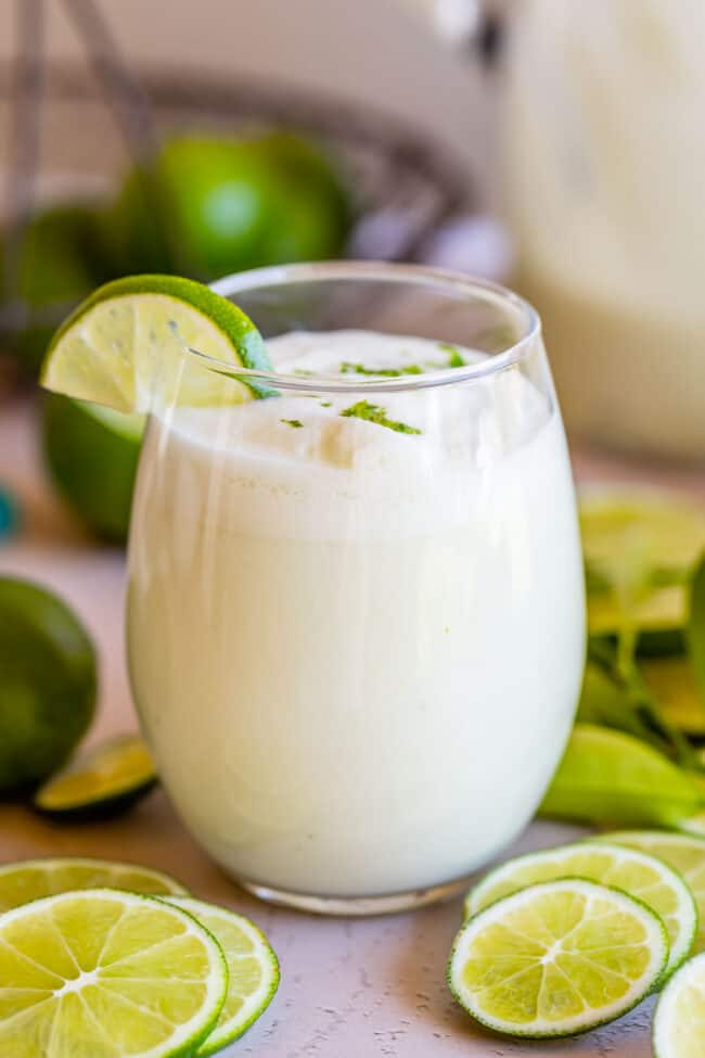 braziilian limeade recipe in a stemless wine glass with lime wedges
