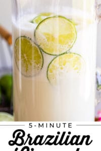 Brazilian Limeade in a clear glass pitcher with lime garnish