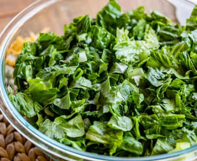 chopped romaine lettuce and green onions in a large clear bowl