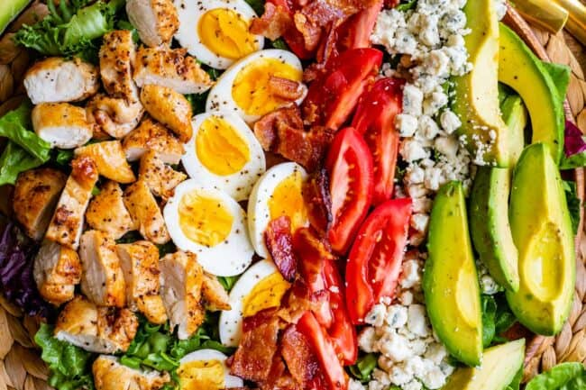 cobb salad ingredients in rows in a bowl
