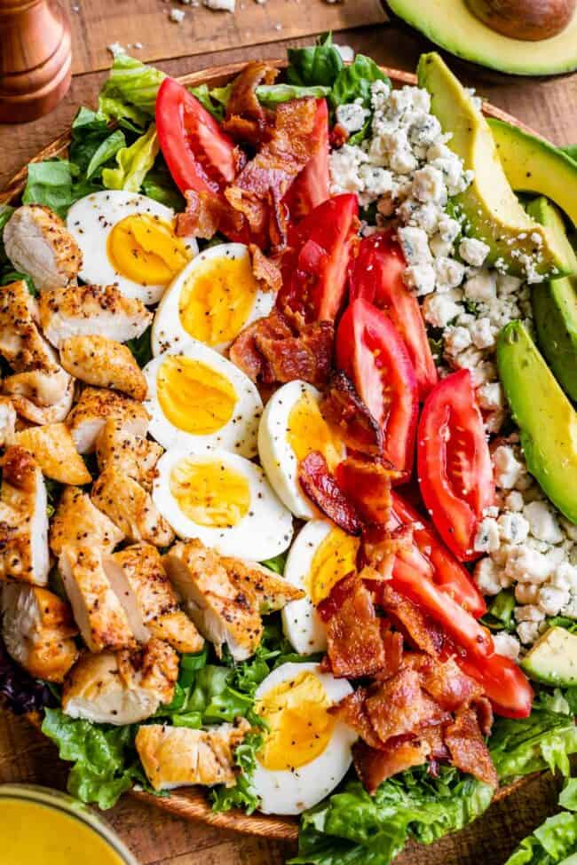 best cobb salad, with ingredients lined up across a wooden plate