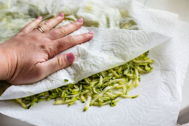 blotting shredded zucchini with paper towels