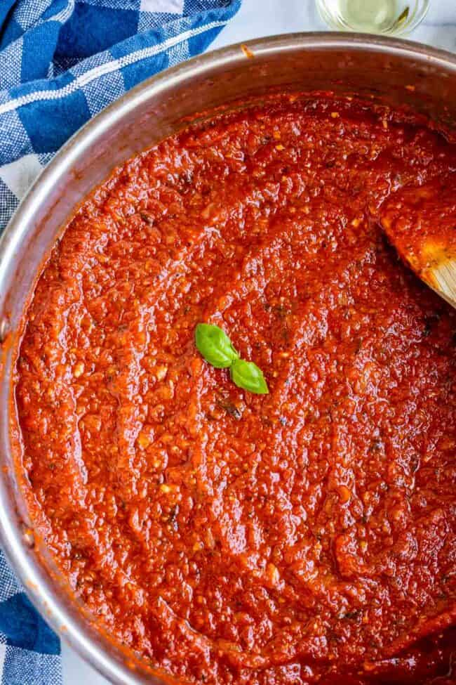 pizza sauce from scratch in a pan with basil garnish