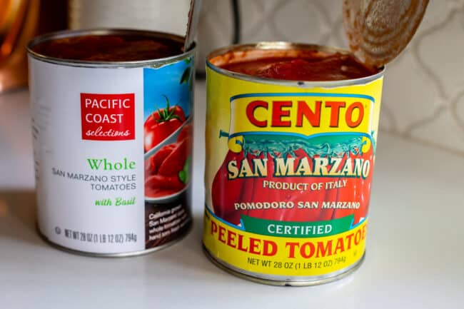 two different brands of canned whole tomatoes on a white countertop