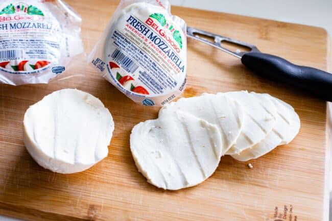 sliced fresh mozzarella cheese on a cutting board