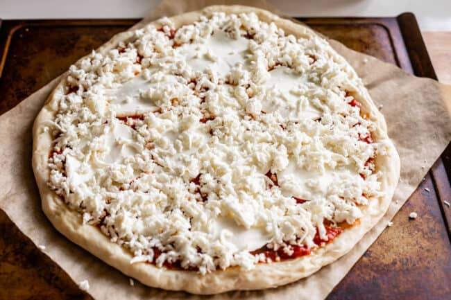 raw pizza dough with sliced and shredded mozzarella on top