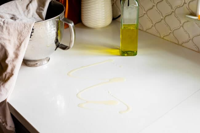 oil drizzled on white countertop to roll out pizza