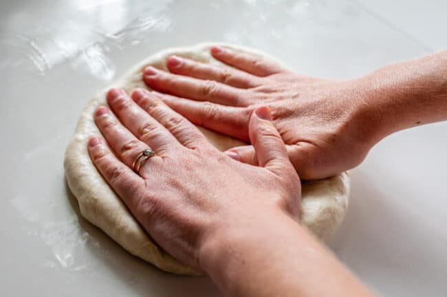 two hands pressing down pizza dough
