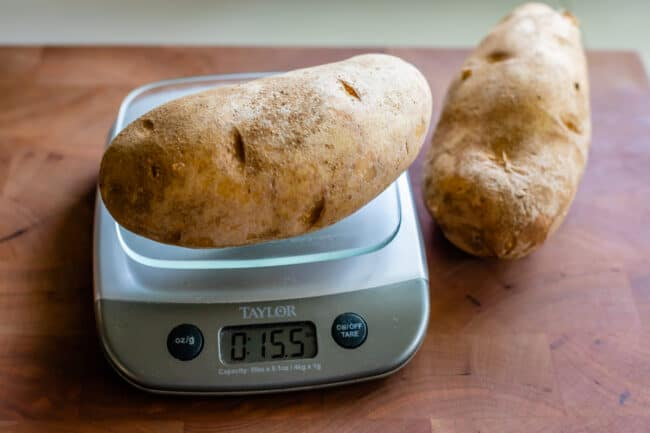 Russet potato on a scale weighing about a pound