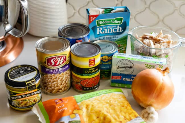 ingredients for chili set up on a counter: canned beans, onion, corn, ranch mix, cream cheese, etc.
