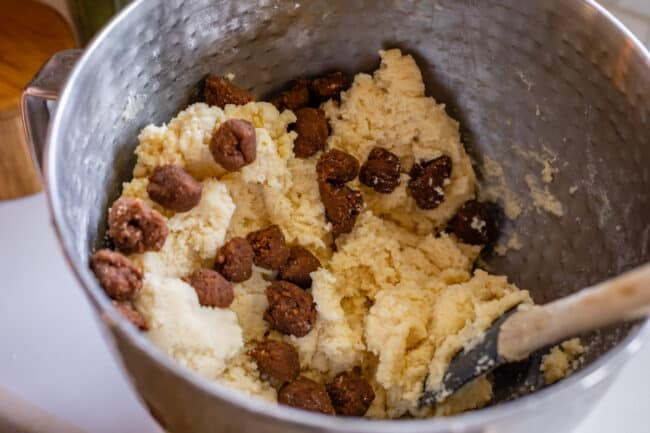snickerdoodle dough in a stand mixer bowl with cinnamon roll filling balls mixed in