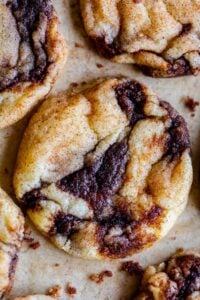soft cinnamon roll cookies with cinnamon swirl on parchment paper