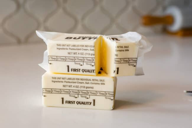 stick of butter on a counter with another stick on top cut in half